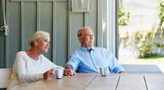 Couple de seniors qui boit un café sur sa terrasse ombragée