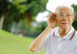 Personne âgée souffrant de presbyacousie qui porte la main à son oreille pour mieux entendre