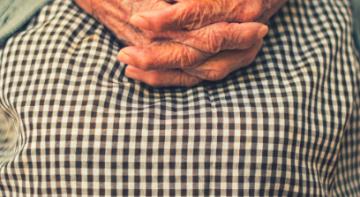 Femme âgée les mains croisées sur les genoux