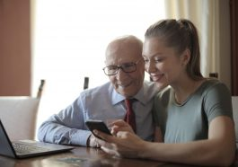 Femme qui montre son smartphone à un vieil homme