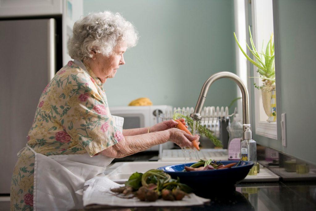 femme âgée nettoie une carotte